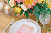 a lovely summer wedding centerpiece of blush, pink and yellow blooms and foliage is amazing and chic