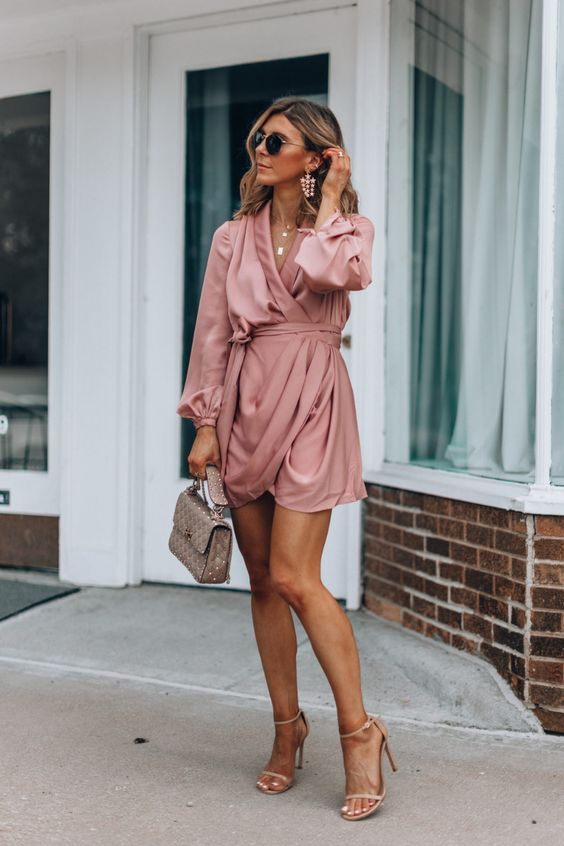a mauve draped mini dress with long sleeves and a sash, a nude bag and nude strappy heels plus statement earrings