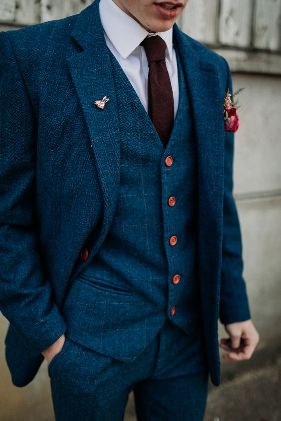 a navy plaid three-piece wedidng suit, a white shirt, a burgundy tie and red button accents