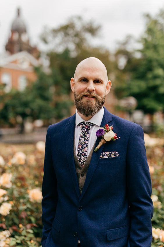 a navy suit, a tweed beige waistcoat, a florla tie and a matchiing handkerchief plus a floral boutonniere