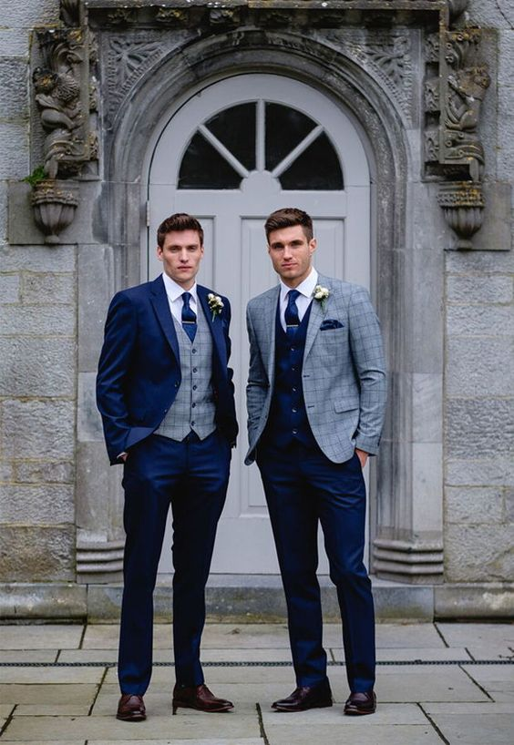 a navy suit with a grey plaid waistcoat, brown shoes and a navy tie plus a vice versa look for the second groom