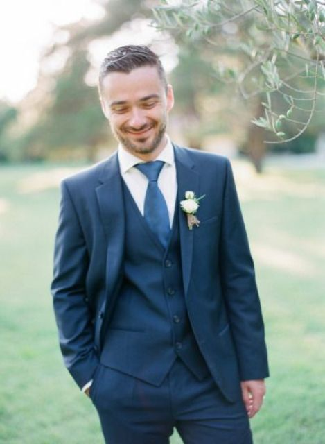 a navy three piece suit, a white shirt and a bright blue tie plus a white boutonniere to refresh the look