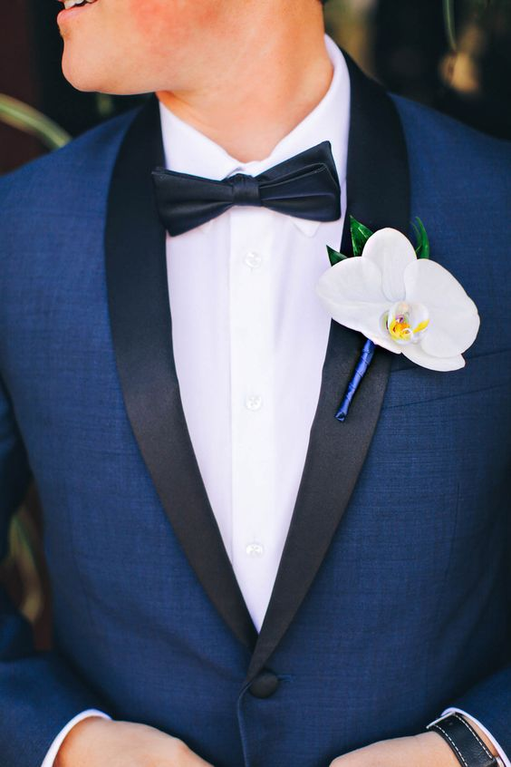 a navy tuxedo with black lapels, a black bow tie and a white orchid boutonniere for a refined tropical groom's look