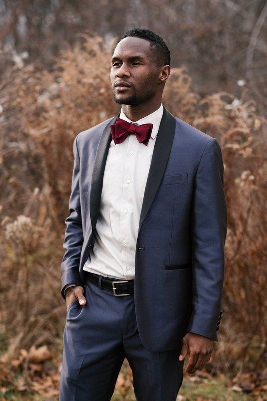 a navy tuxedo with black lapels, a white shirt, a burgundy bow tie and a black belt is a gorgeous fall look