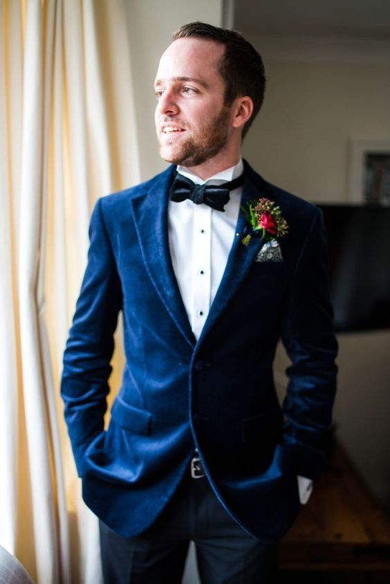 a navy velvet blazer, a white shirt with black buttons, a black bow tie and a bright floral boutonniere