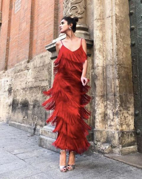 a red fringe maxi dress on spaghetti straps, silver shoes, statement earrings and a clutch for a chic fall wedding guest look