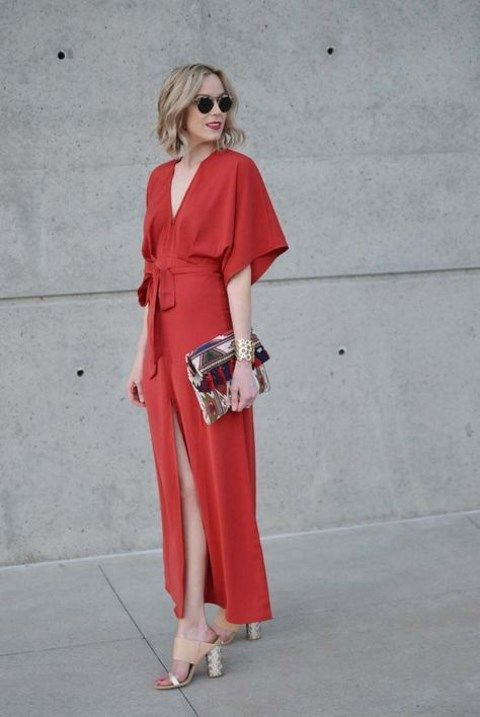 a red maxi dress with a deep neckline, wide sleeves, a sash, tan and silver heels and a silver bag for a fall wedding