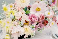 a refined pastel summer wedding centerpiece of yellow, blush, mauve and blue blooms features much dimension