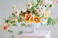 a refined summer wedding arrangement of light pink, peachy and yellow blooms and textural greenery