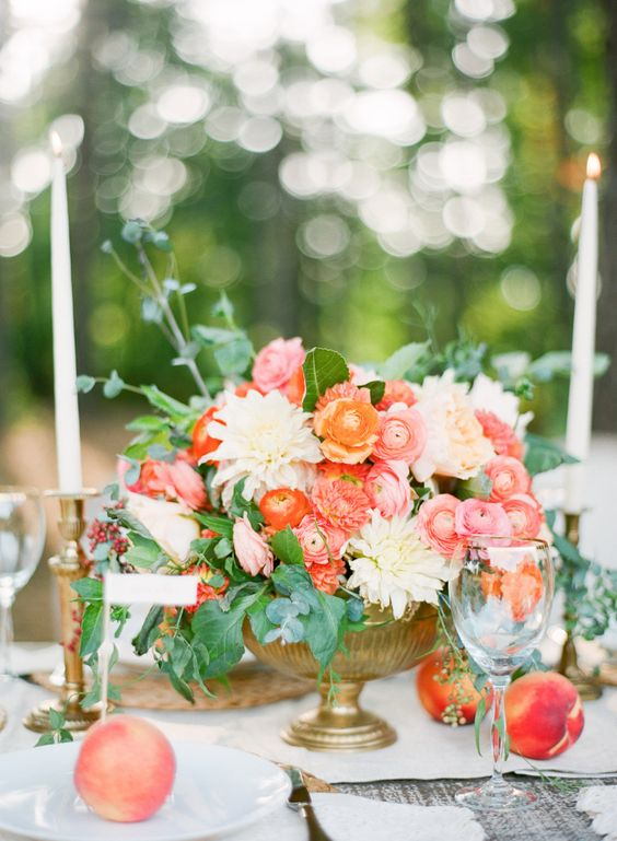 a refined summer wedding centerpiece of a gold urn, red and pink and white flowers, foliage is chic