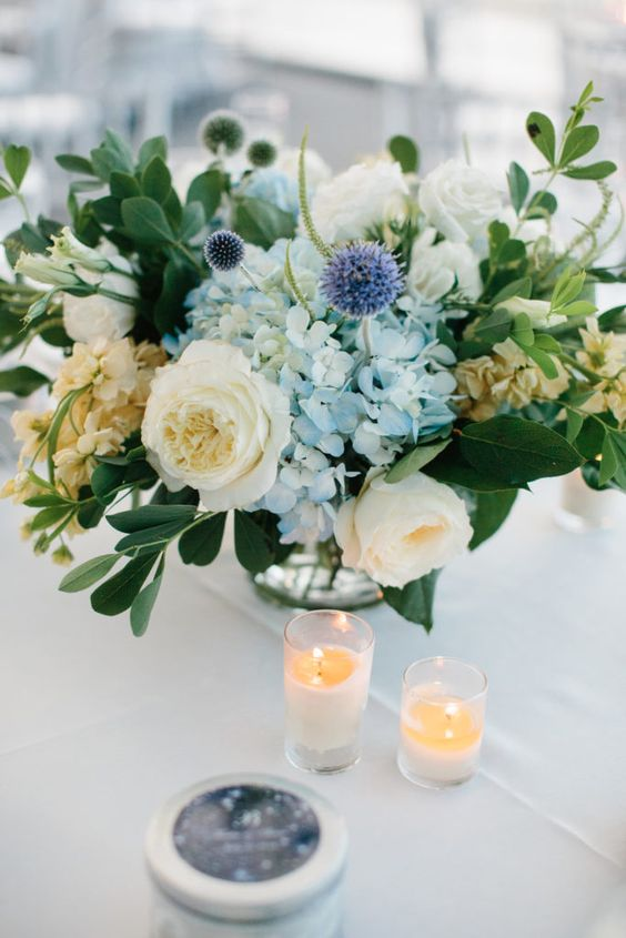 a refreshing summer wedding centerpiece of neutral and blue blooms, allium and textural greenery