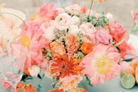 a romantic and bright summer wedding centerpiece of orange, red, pink and blush blooms and greenery plus citrus