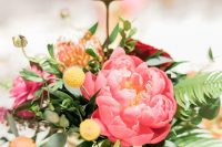 a romantic colorful summer wedding centerpiece with orange and coral pink blooms, billy balls and a table number