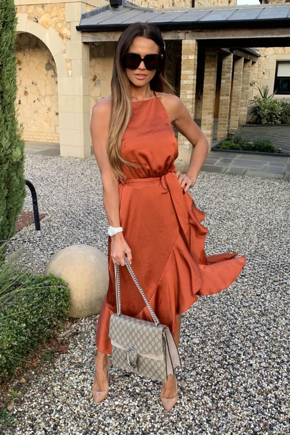 a rust colored wrap midi dress with a halter neckline and ruffles, with nude shoes and a grey bag for summer or fall