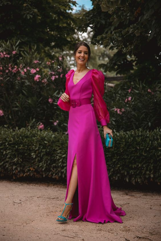a statement look with a hot pink maxi dress, red balloon sleeves, a front slit, turquoise heels and a mini clutch for a bold outfit at a formal wedding