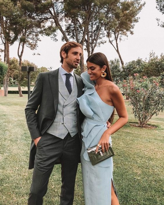 a statement pale blue maxi fitting dress with a sculptural bodice and one shoulder plus a side slit, statement earrings and a clutch for a formal wedding