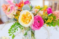 a super colorful summer wedding centerpiece of hot pink, peachy and red blooms, leaves and berries is chic