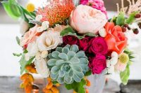 a super colorful summer wedding centerpiece of red, hot pink, fuchsia, orange blooms, a succulent and kumquats