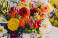 a super vibrant summer wedding centerpiece of red, yellow, purple, white, pink and rust blooms and greenery