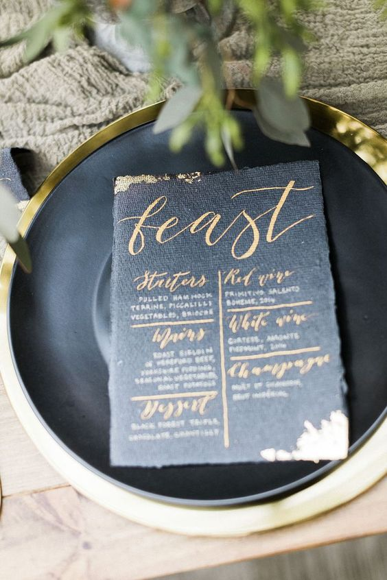 a textural black wedding menu with gold calligraphy and a textural edge