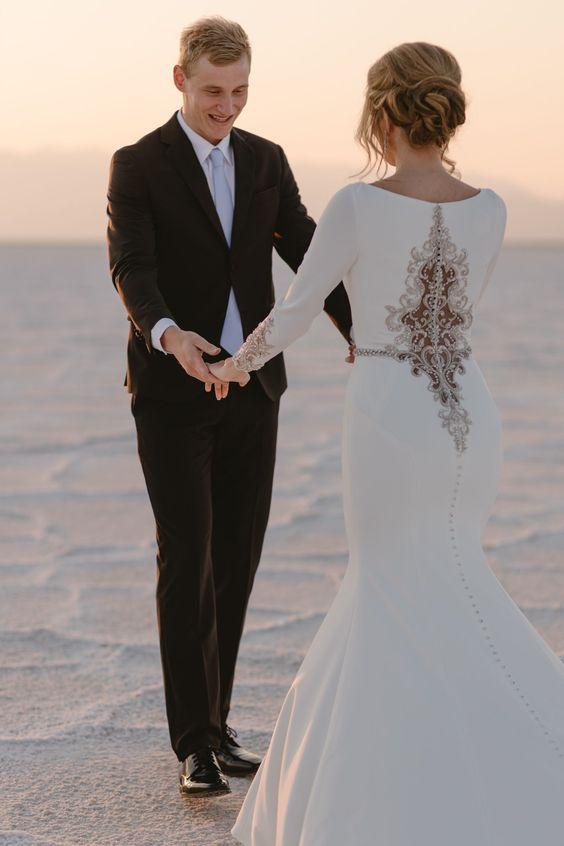a unique plain white mermaid wedding dress with a unique lace and rhinestone detail on the back and matching sleeves is wow