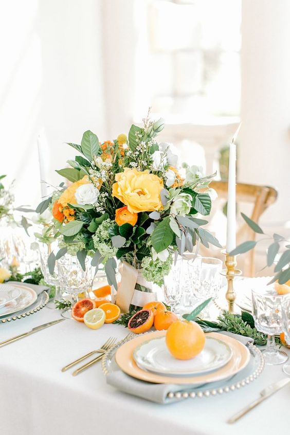a vibrant summer wedding centerpiece of foliage, some white and yellow blooms and touches of orange