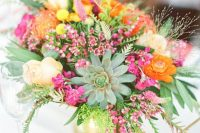 a vibrant summer wedding centerpiece of pink, orange, yellow and fuchsia blooms, foliage and a statement succulent