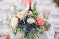 a vibrant summer wedding centerpiece of thistles, blush and pink blooms and greenery is chic and bold
