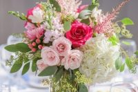 a vibrant wedding centerpiece of white, light and hot pink blooms, berries and foliage is lovely and chic