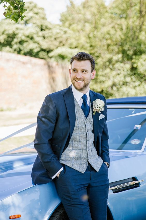 a vintage-inspired look with a navy suit, a grey plaid waistcoat, a navy tie and a white shirt