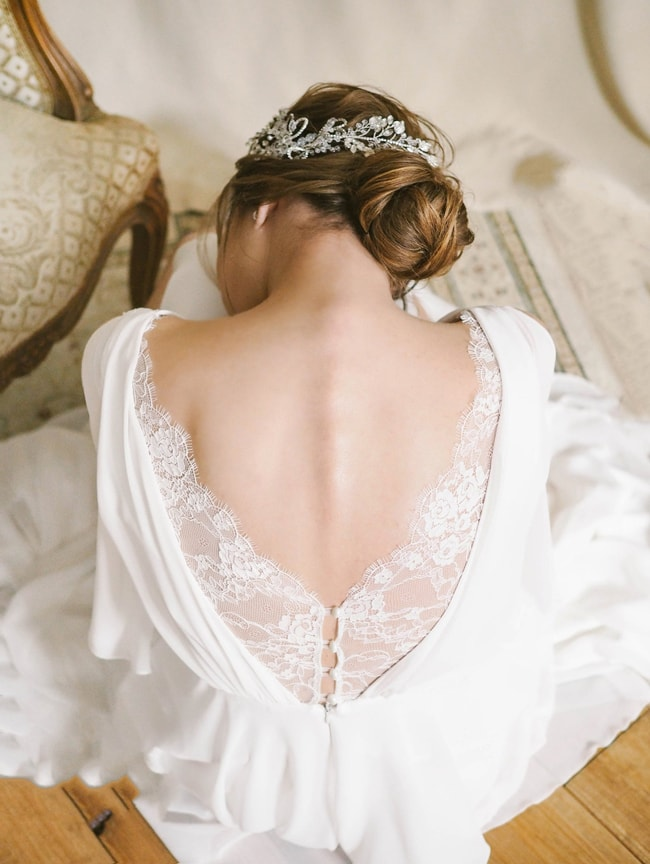 a vintage plain wedding dress with draperies and a lace detail with buttons on the back is a beautiful and refined idea