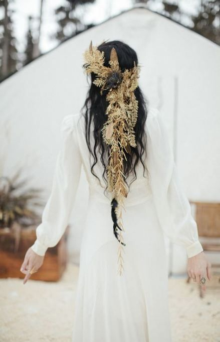 a whimsical boho chic headpiece of dried herbs and large feathers is a cool idea for a wild free-spirited bride