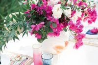 a white textural vase with white and hot pink blooms and greenery is bold and chic