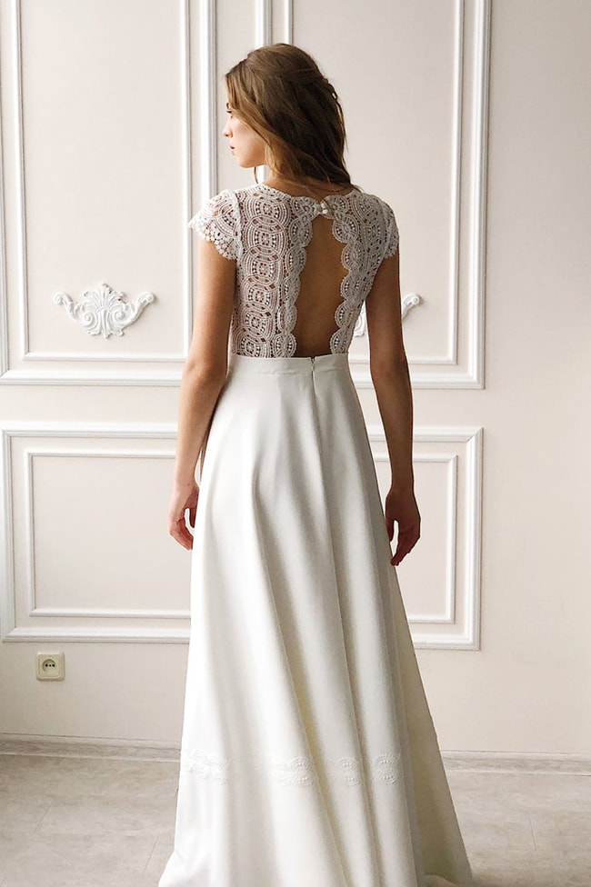 an A-line wedding dress with a boho lace bodice and a plain skirt with a train, a cutout back of boho lace is amazing