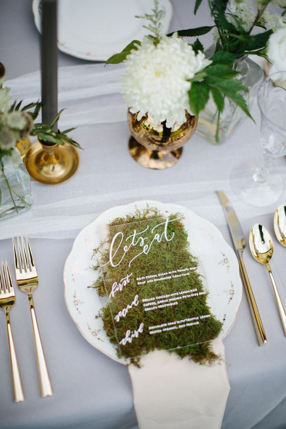 an acryclic and moss wedding menu with white calligraphy and printing is a great natural touch to the space