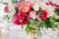 an elegant summer wedding centerpiece with much color – fuchsia and light pink blooms and much foliage