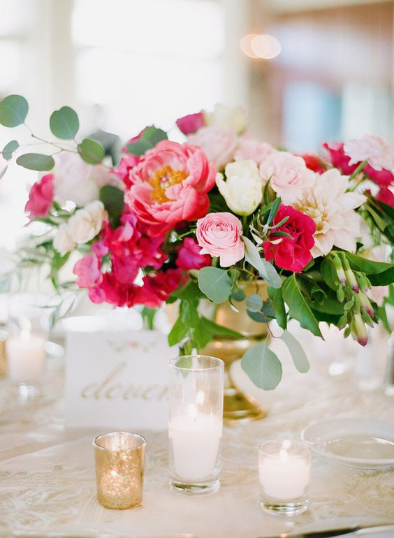 an elegant summer wedding centerpiece with much color   fuchsia and light pink blooms and much foliage