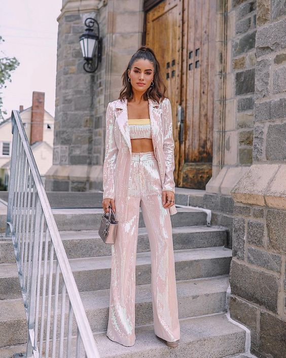 an iridescent sequin pantsuit and a matching crop top, a silver bag and heels for a disco or NYE wedding