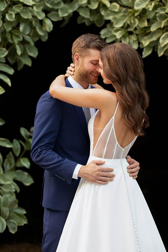 an ultra-modern and refined A-line wedding dress with an illusoin back done with sheer fabric, a plain skirt with buttons is chic