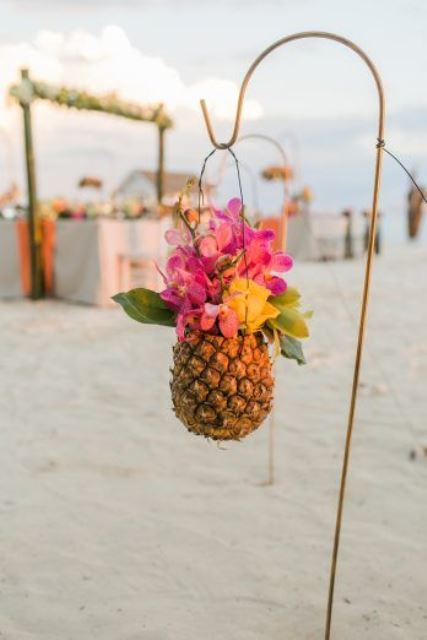 decorate your wedding aisle with bright blooms in pineapples to give a strong tropical feel to the wedding