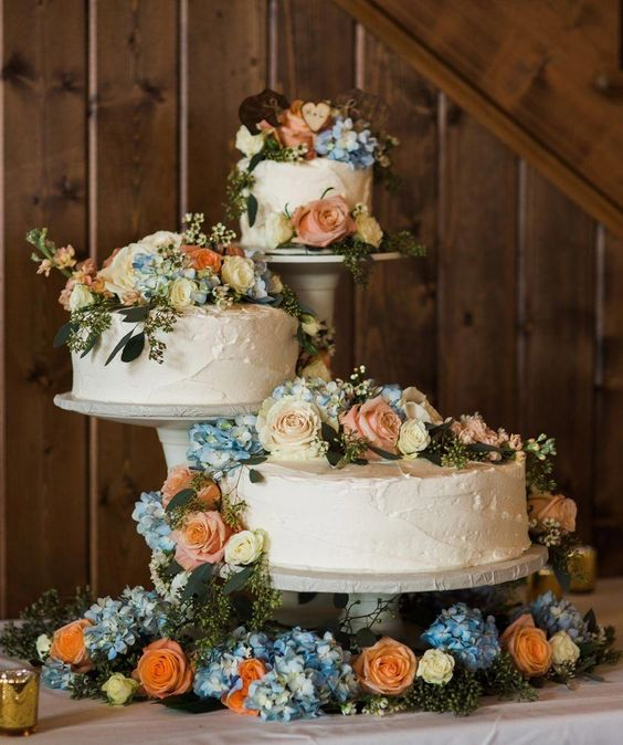 neutral wedding cake stands with blue, peach and white blooms and greenery on the table and cakes