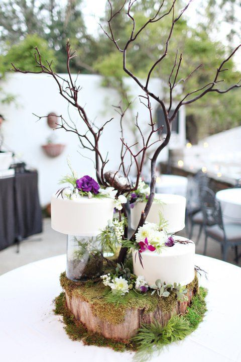wedding cakes placed on a wood slice with moss and greenery, blooms and branches will be a nice idea for a woodland wedding