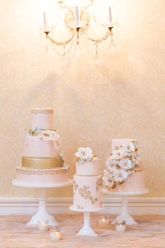 white wedding cake stands of various height, candles and blush and gold cakes with neutral sugar blooms
