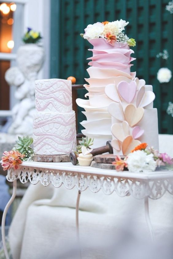 wood slices as cake stands for a whole arrangement of colorful wedding cakes with blooms and hearts will give a rustic feel to the sweet table