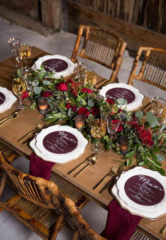 a barn wedding tablescape with an uncovered table, a greenery and burgundy bloom runner, burgundy linens and touches of gold