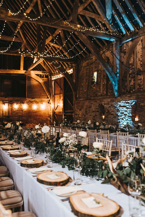 a beautiful barn wedding tablescape with a greenery and white rose runner, wood slice chargers and antlers