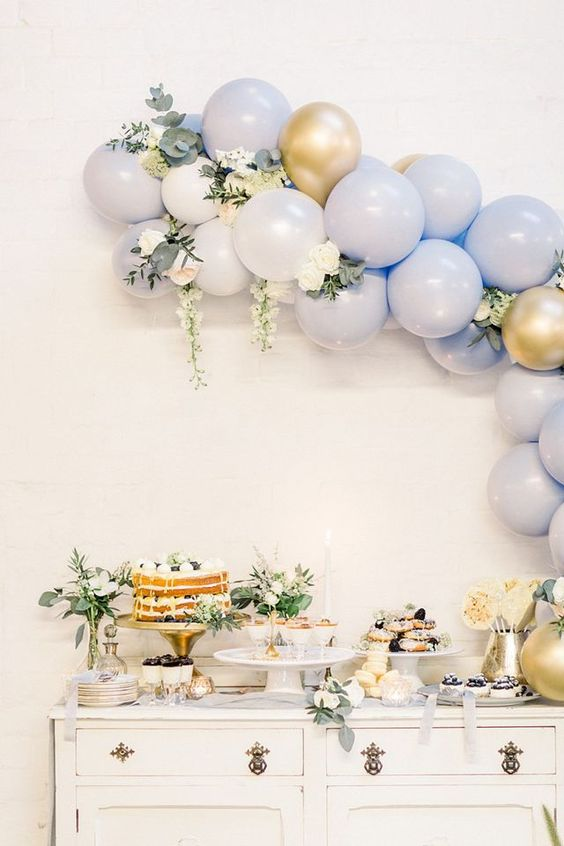 a beautiful blue, white and gold balloon garland with neutral blooms and greenery is a cool decoration for your wedding