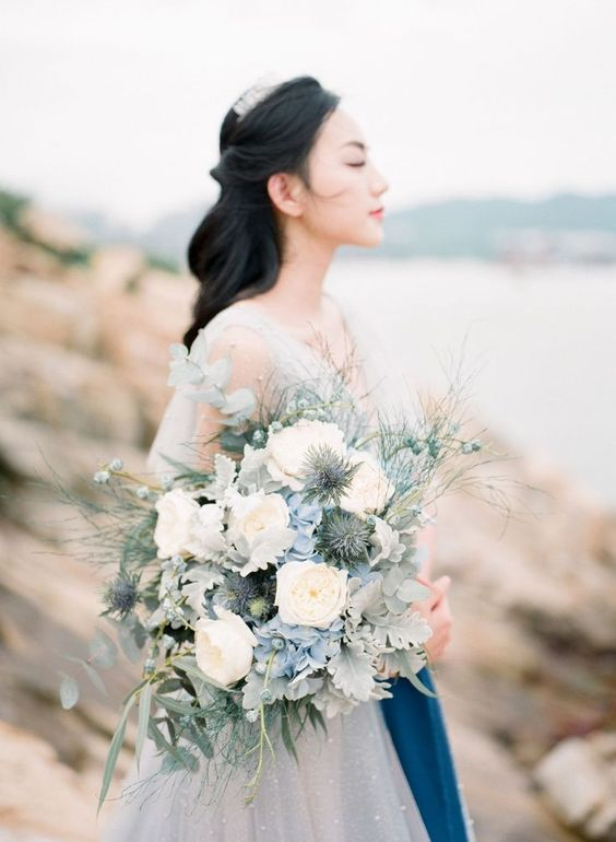 a beautiful coastal wedding bouquet of white, powder blue, pale leaves and twigs
