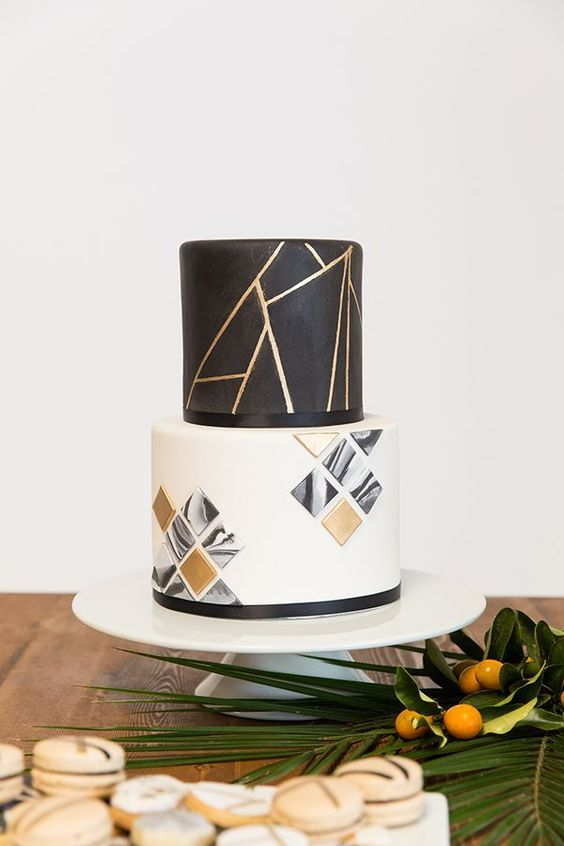 a black, white and gold wedding cake with geometric decor and 3D geometric tiles on the lower tier is a lovely idea to rock