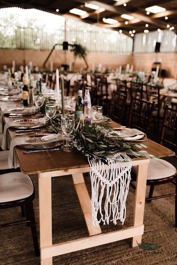 a boho barn wedding tablescape with a macrame and eucalyptus runner, thin and tall candles and hammered metal chargers